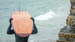 An unknown man holding surfboard on head hiding his face