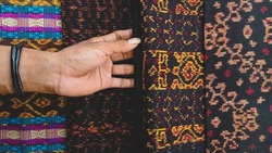 An unknown man's hand touches a traditional hand-woven fabric with an ethnic motif, namely Ende Lio from Flores Island, Indonesia.