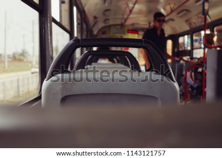 An unknown person buys tickets for a tram. Armchairs in a tram #1143121757