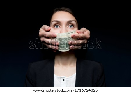 An unknown person closes mouth to a woman director of a large firm with a stack of hundred-dollar bills. Purchase of silence, blackmail, corruption in business and state structures Foto stock ©
