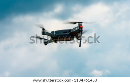 an unmanned helicopter flying with a digital camera. Demon with a digital camera of high resolution. The flying camera takes photos and video. A drone with a professional camera against a blue sky wit