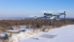 An unmanned quadcopter with a digital camera flies over the city in winter. The camera flies and takes pictures of the forest, the city. Close-up, blurred background. Modern technology, video filming