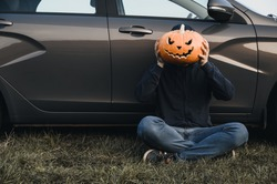 An unrecognizable adult man sits near a car on the grass and holds in front of his face a carved pumpkin for Halloween, outdoors. Copy space. Faceless concept
