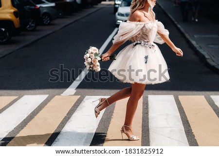 an unrecognizable bride in a short white wedding dress with a bouquet runs across the road in the city at a pedestrian crossing Photo stock ©