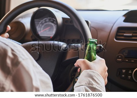 An unrecognizable female drinking beer while driving car. Concepts of driving under the influence, drunk driving or impaired driving