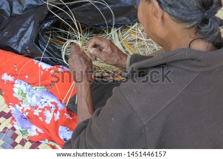 An unrecognizable Indigenous Australian Aboriginal woman basket weaving in Arnhem Land in the Northern Territory of Australia #1451446157