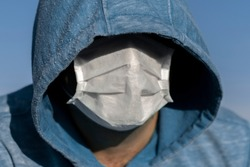 An unrecognizable male face is hidden by a hood and a medical mask. Close-up portrait.