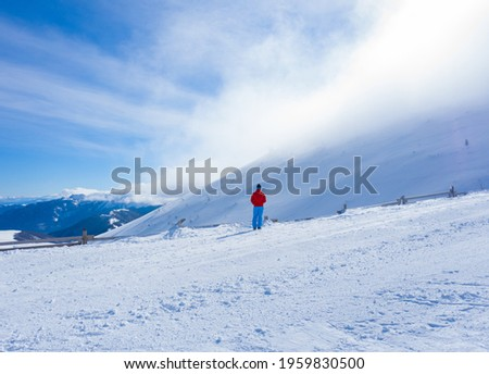 An unrecognizable man standing in the middle of a snowfield on a cold winter day Stock photo ©