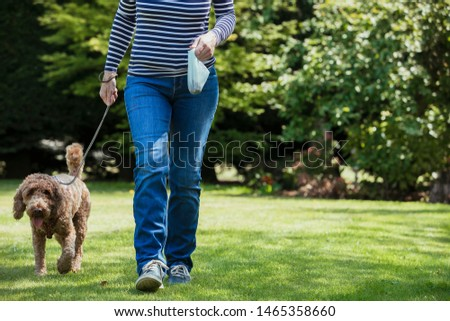 An unrecognizable person carrying a poo bag as she takes her dog for a walk in a public park. #1465358660