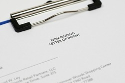 An unrecognizable person filling non-binding letter of intent. Close-up view