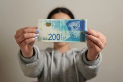An unrecognizable person holding a 200 Israeli Shekel banknote - business, finance concept