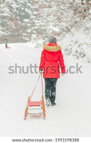 An unrecognizable woman with a sleigh walking in the snowfield in winter Stock photo ©