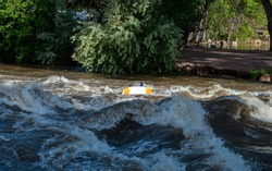 An unrecognizable, yet clearly experienced thrill seeker, capsizes his kayak on the rapids of a flooded river in Colorado.