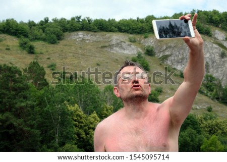 An unshaven middle-aged man takes off taking a selfie against the backdrop of the mountains. Bespectacled photographer without clothes on nature holds the phone in his left hand. Funny face while