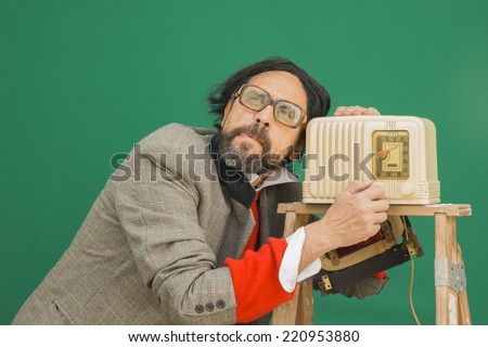 An untidy bizarre man, wearing big patched glasses and a toupee, listening to a radio station on an antique bakelite tube radio on a ladder, over green background