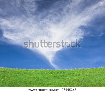 An unusual cloud formation over a green hillside in California.