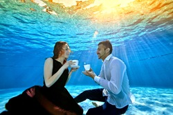 An unusual loving couple, a guy and a girl, look at each other, sitting underwater at the bottom of the pool with white cups in their hands. Surrealism. The concept of tranquility and serenity