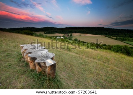 An unusual shaped wooden bench looks over some fields and trees.  The sunset lights up some clouds in the sky.