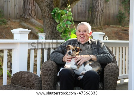 An upbeat joyful retired elderly man at home relaxing with dog
