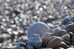 An uplifting beautifully round grey pebble in the middle foreground. Large pebbles surround it and  small bokeh, grey sparkle on the left from wet pebbles glistening. Some glisten blue from bluest sky