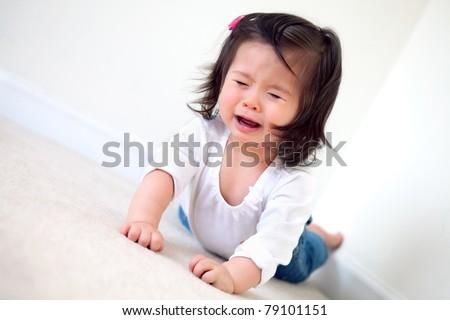 an upset baby girl crying on the floor - stock photo