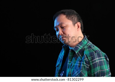 An upset mature Asian man. Blue lighting on face.