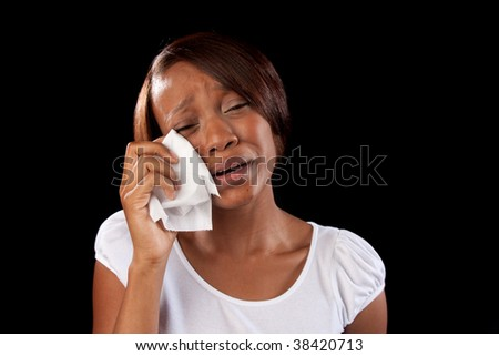 an upset woman cries and wipes her eyes with a tissue