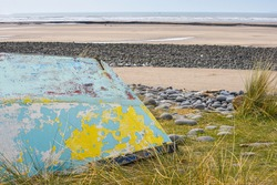 An upturned small boat washed up on the shoreline of a beautiful unspoiled beach