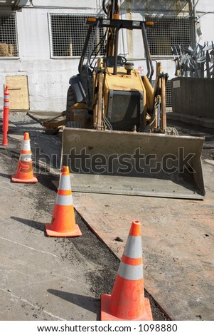 An urban construction zone with a front loader tractor, orange cones and steel plates.