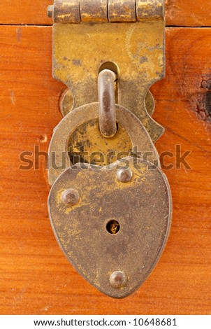 An very small padlock on an old cedar box. Scratches & imperfections at 100%