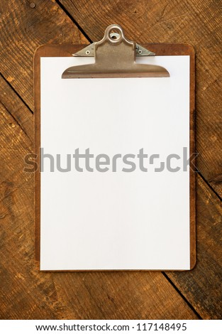 An vintage clipboard on a old wooden desk, with regular white blank paper.