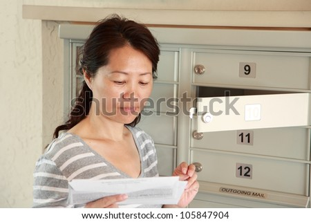 An woman opening a letter from a mailbox
