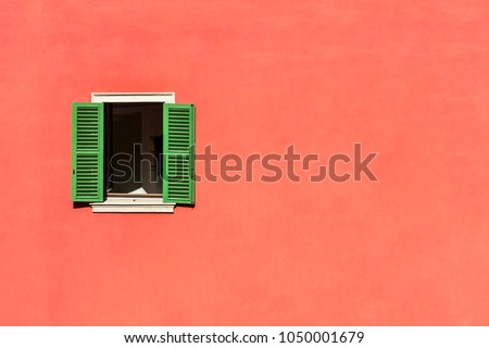 An wood vintage window with green shutters on the plastered stone wall in italian style.