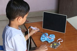 An 8 year old child is learning to make drone in online coding class with black screen tab. electric Soldering iron in kids' hand. closeup image.  concept kids coding classes. selective focus kids.