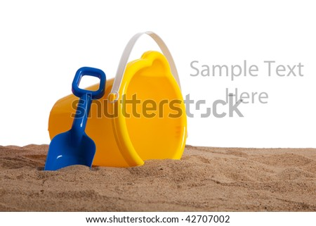 An yellow bucket and blue shovel on a sandy beach with copy space on a white background