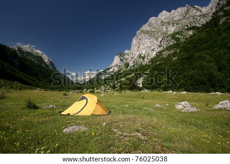 an yellow tent on a green meadow at the foot of a mountain. Ropojana Valley, Prokletije Mountains, or Albanian Alps, Montenegro