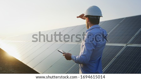 An young engineer is checking with tablet an operation of sun and cleanliness on field of photovoltaic solar panels on a sunset. Concept:renewable energy, technology,electricity,service, green,future