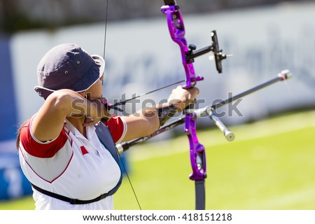 An young girl is shooting with a recurve bow during un open archery competition.