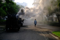 An young Indian woman is walking along a road filled with smoke emitted from a machine in the morning. Indian lifestyle.
