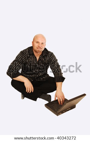 An young man sitting on the floor and working with his laptop.