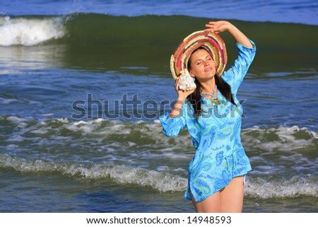 An young pretty girl holding a sea shell
