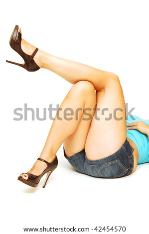 An young woman in short jeans shorts is laying on the floor in high heel and showing her beautiful legs.