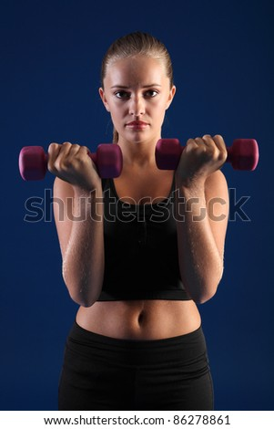 Anaerobic exercise by beautiful young caucasian fitness woman using hand weights for bicep curls wearing black sports bra.