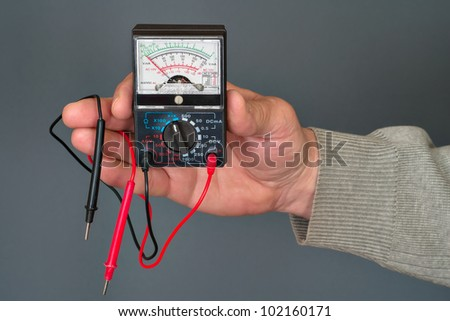 analog multimeter with wires in a man's hand