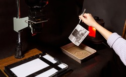 Analog photo printing. The photographer prints a black and white photograph. Photolaboratory. Red light