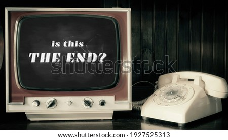 Analog scene with a rotary phone and a vintage TV (broken glass): an end title, as seen in old horror movies, asking Is this The End?  Stockfoto ©