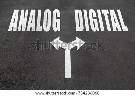 Analog vs digital choice concept, two direction arrows on asphalt.