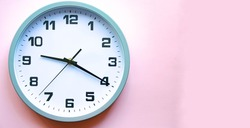 Analog white clock on a pink background. Clock in close up. Place for text. Business, are you ready.