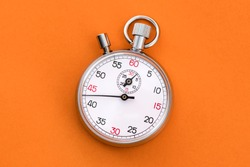 Analogue metal stopwatch on the orange background.
