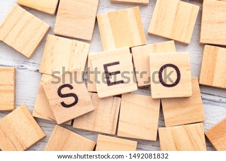 Analyse and optimize business strategy, marketing jargon and website statistic research conceptual idea with wooden tile spelling out the acronym SEO (search engine optimization) on wood background